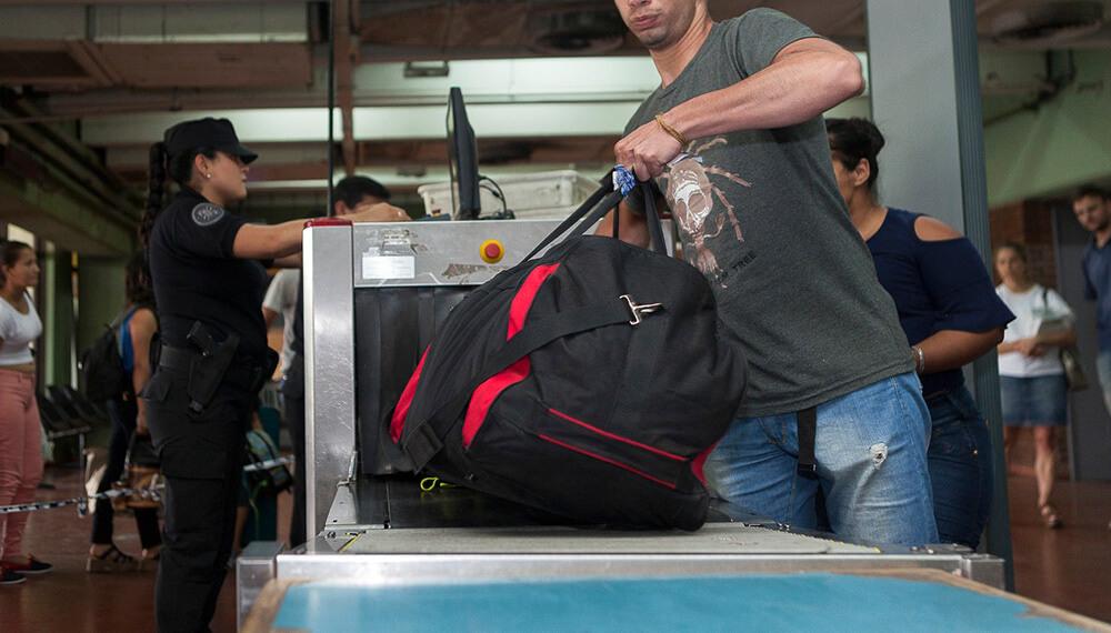 hombre con valija en escáner de aeropuerto