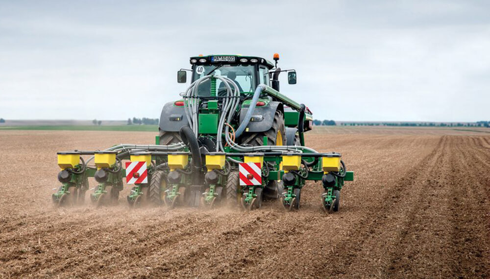 máquina agrícola sembrando maíz en un campo
